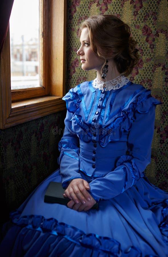 Молодая женщина в голубом винтажном платье сидя в coupe около выигрыша стоковое фото rf