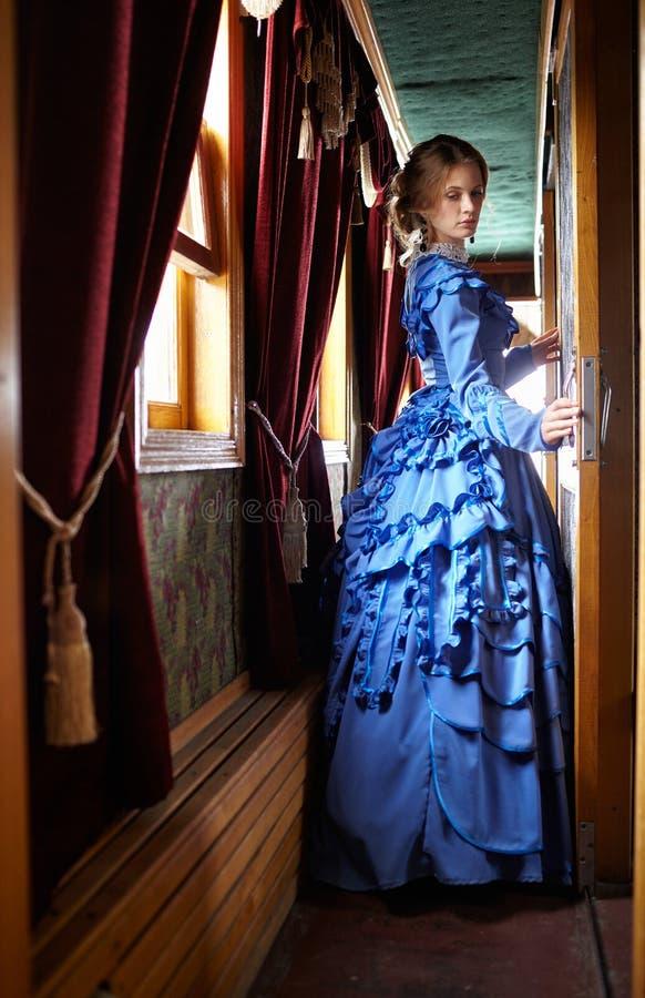 Молодая женщина в голубом винтажном платье стоя в коридоре ретро стоковые фотографии rf