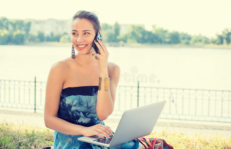 Молодая женщина в голубом платье говоря на мобильном телефоне outdoors стоковое фото rf