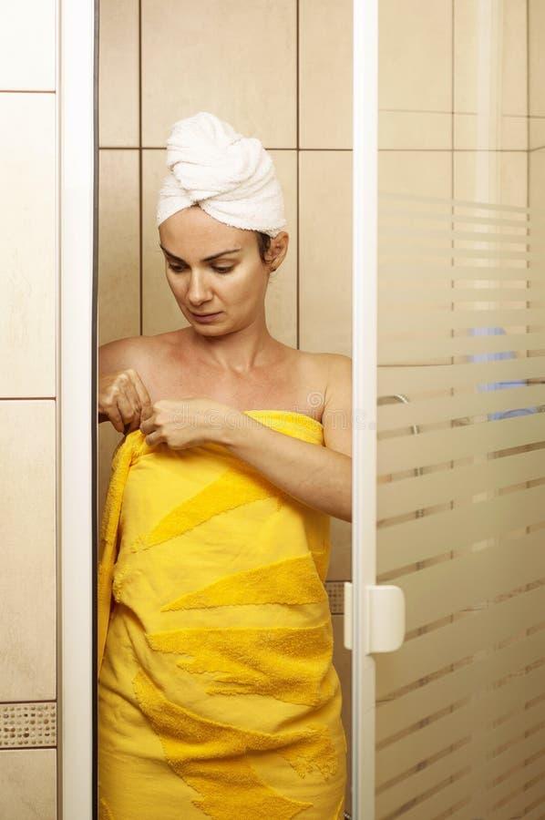 Молодая женщина в ливне аранжируя ее полотенце стоковое фото rf