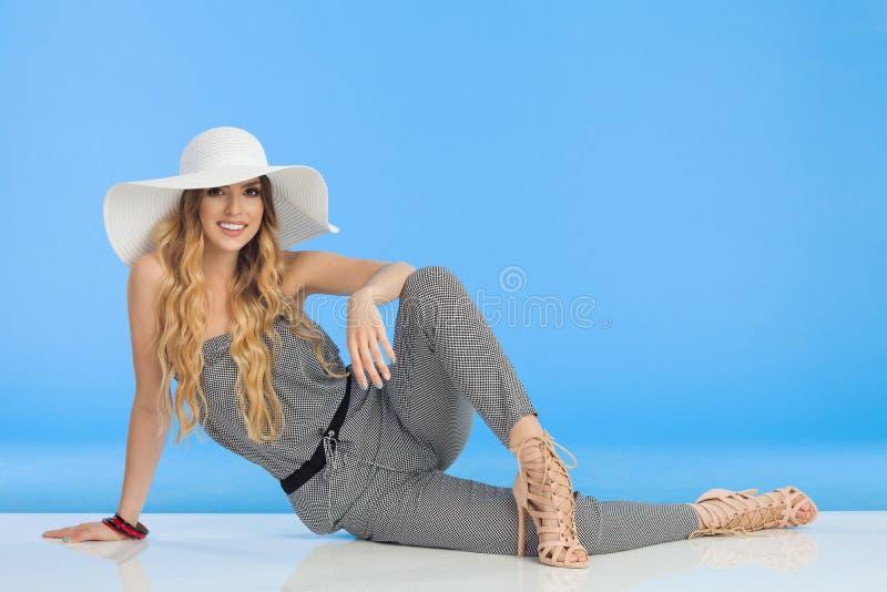 Молодая женщина в комбинезоне, белой шляпе Солнця и высоких пятках ослабленный сидеть стоковое фото rf