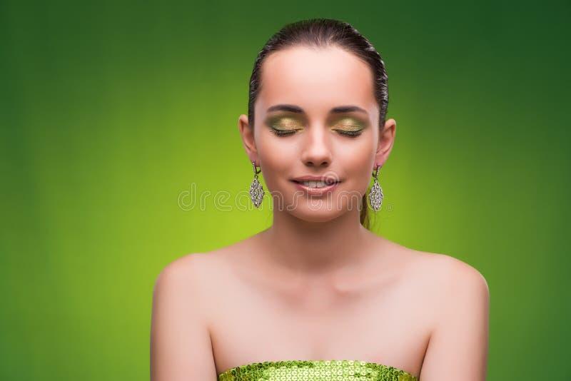 Молодая женщина в концепции красоты на зеленой предпосылке стоковые изображения rf