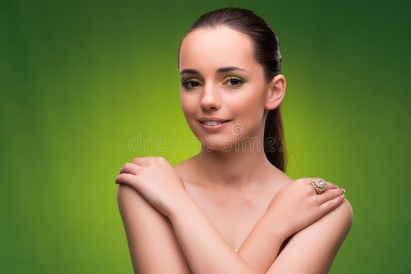 Молодая женщина в концепции красоты на зеленой предпосылке стоковая фотография
