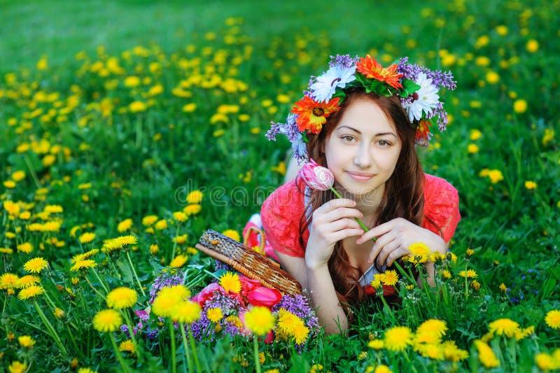 Молодая женщина в красном платье лежа на траве в луге стоковые фотографии rf
