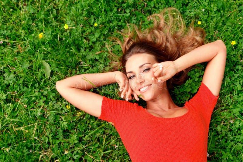 Молодая женщина в красном платье лежа на траве стоковое изображение