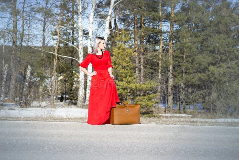 Молодая женщина в красном платье на дороге с красным багажом стоковая фотография rf