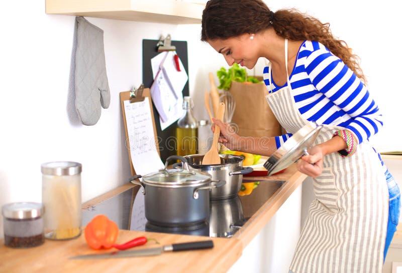 Молодая женщина в кухне подготавливая еду стоковое изображение