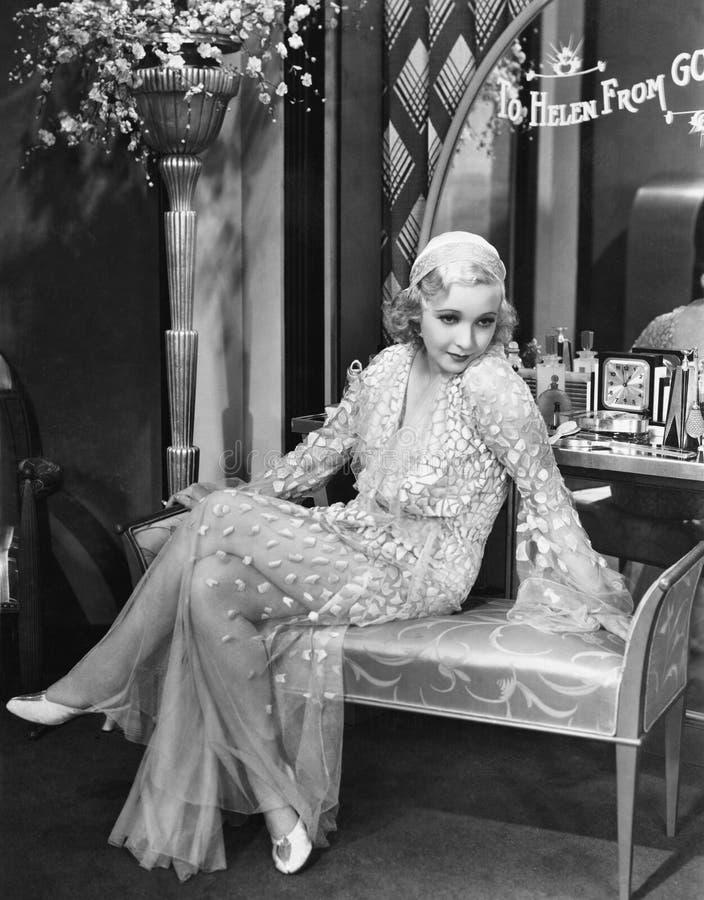 Молодая женщина в мантии вечера сидя на обитом стенде (все показанные люди более длинные живущие и никакое имущество не существуе стоковые фотографии rf