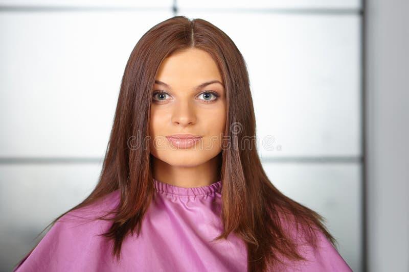 Молодая женщина в мантии вырезывания волос. стоковые изображения