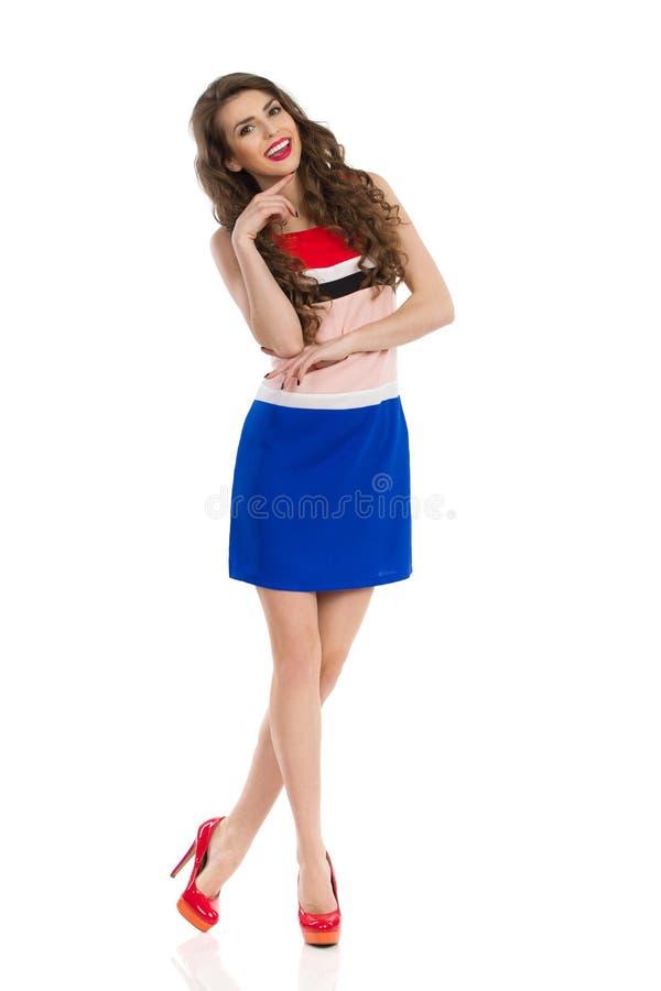 Молодая женщина в мини платье и высоких пятках стоит с пересеченными ногами и усмехаться стоковые изображения rf