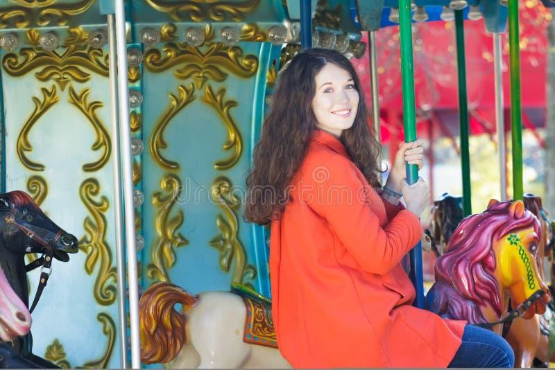 Молодая женщина в оранжевом портрете carousel пальто верхом внешнем стоковое фото