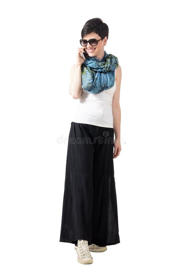 Молодая женщина в одеждах и солнечных очках лета говоря на умный усмехаться телефона стоковая фотография rf