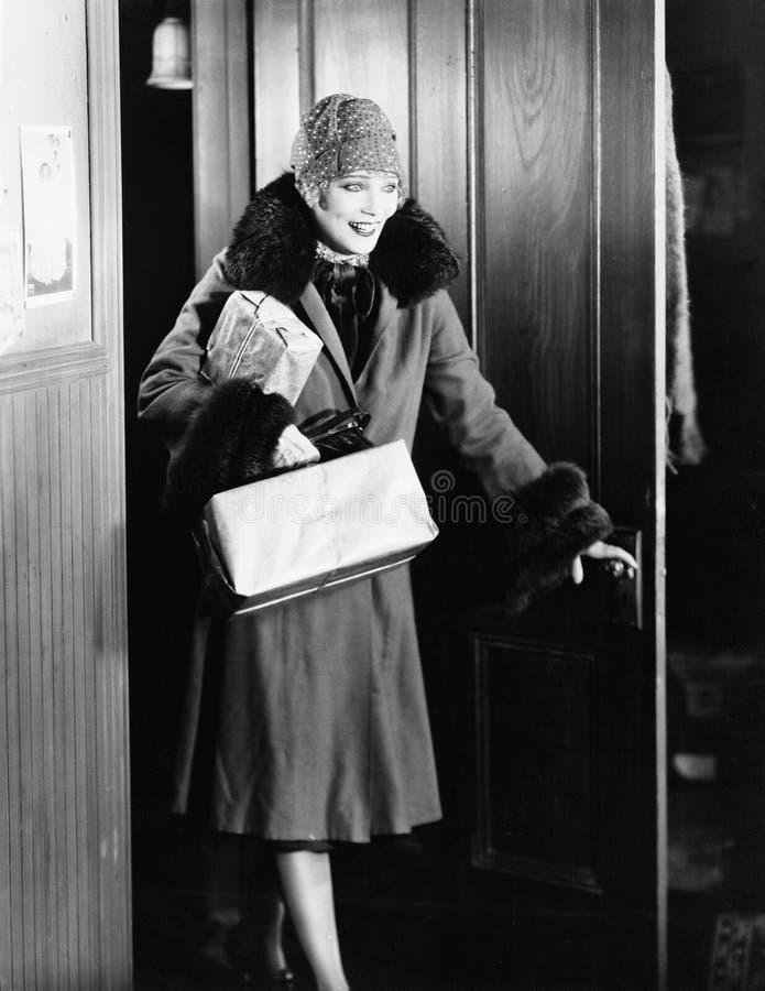 Молодая женщина в пальто и шляпе входя в в комнату (все показанные люди более длинные живущие и никакое имущество не существует W стоковые фотографии rf
