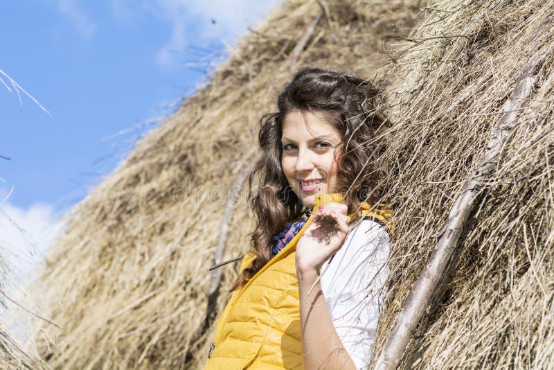 Молодая женщина в поле соломы с связками день осени солнечный стоковая фотография rf