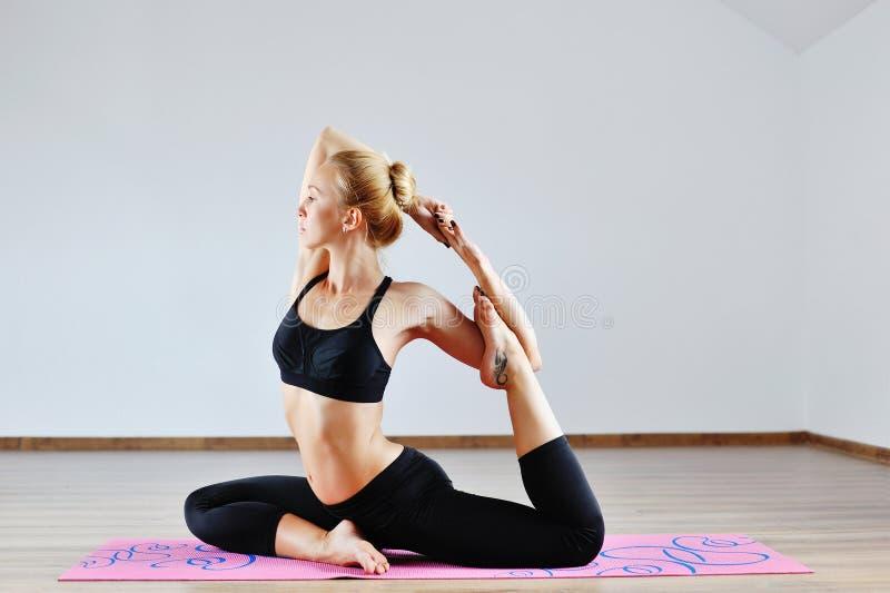 Молодая женщина в положении йоги внутри помещения стоковые фото