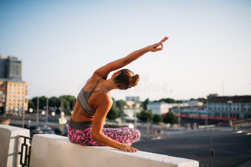 Молодая женщина в представлении йоги, город на предпосылке стоковое фото