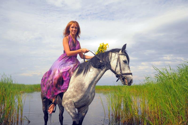 Молодая женщина в платье на лошади стоковое изображение