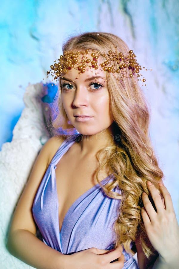 Молодая женщина в платье принцессы на предпосылке феи зимы стоковая фотография