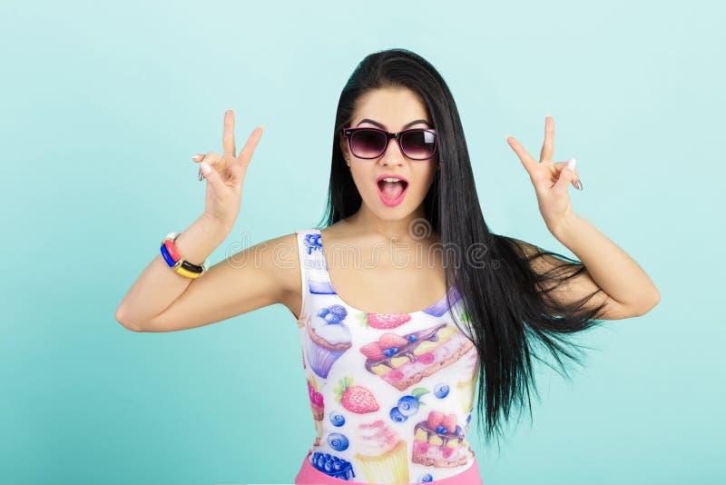 Молодая женщина в розовой верхней части танка на голубой предпосылке удивленная девушка в солнечных очках показывая 2 пальцы или  стоковое фото rf