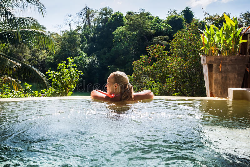 Молодая женщина в роскошной гостинице в бассейне стоковые фотографии rf