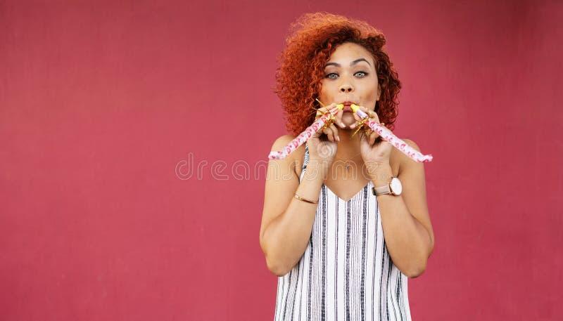 Молодая женщина в свистках партии шаловливого настроения дуя стоковое фото rf