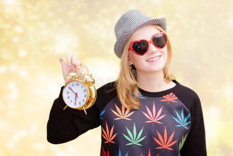 Молодая женщина в солнечных очках и удерживании шляпы fedora стоковая фотография rf