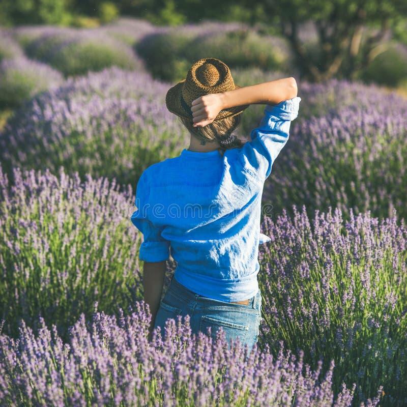 Молодая женщина в соломенной шляпе наслаждаясь полем лаванды, квадратным урожаем стоковые фото