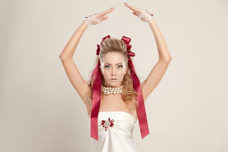 Молодая женщина в стиле куклы при красные смычки, держа ее руки вверх стоковое изображение rf