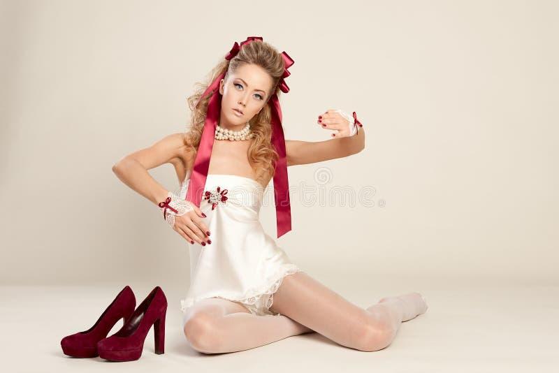 Молодая женщина в стиле куклы с красными смычком и красным цветом обувает sitti стоковые изображения rf