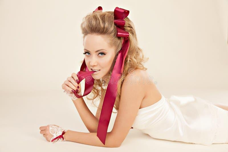 Молодая женщина в стиле куклы с смычками красного цвета и flirty взглядами стоковые фотографии rf