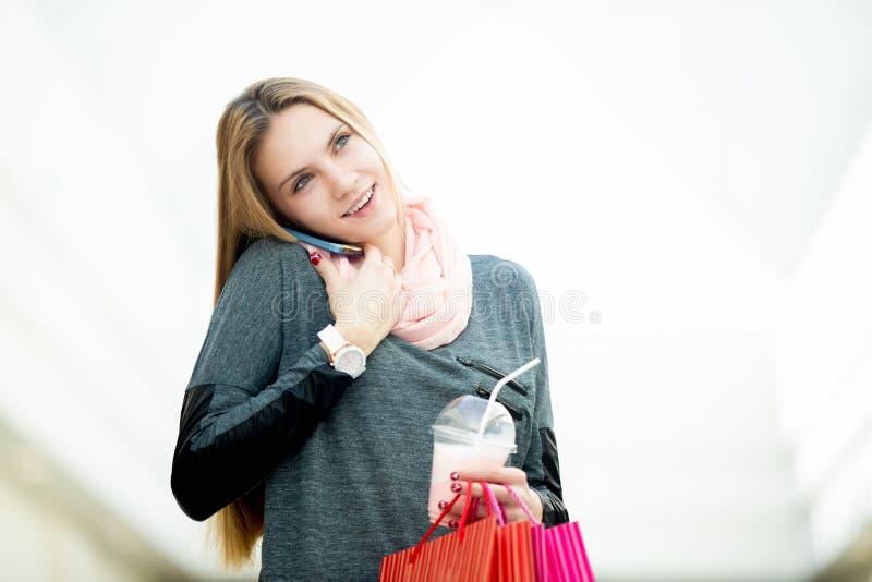 Молодая женщина в супермаркете говоря на мобильном телефоне держа shopp стоковые фотографии rf