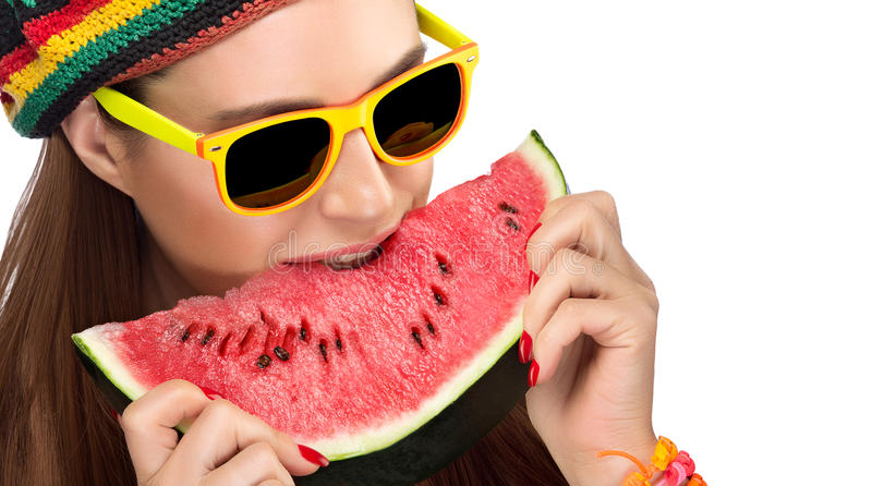 Молодая женщина в ультрамодных солнечных очках есть арбуз стоковые изображения