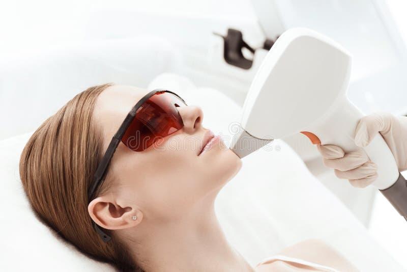 Молодая женщина в ультрафиолетовых защитных стеклах получая заботу кожи лазера на стороне стоковое изображение rf