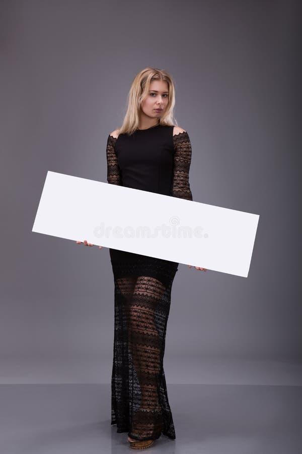 Молодая женщина в черном платье держа пустой плакат стоковое фото