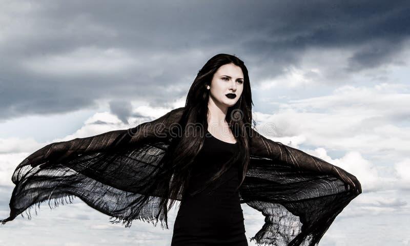 Молодая женщина в черные выпорхнутые одежды стоковое фото