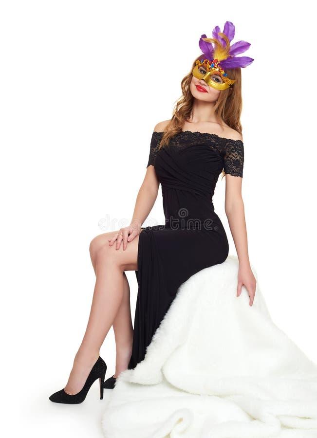 Молодая женщина в черных мантии вечера и маске масленицы Сидите на белом мехе Праздник и концепция партии стоковое изображение rf
