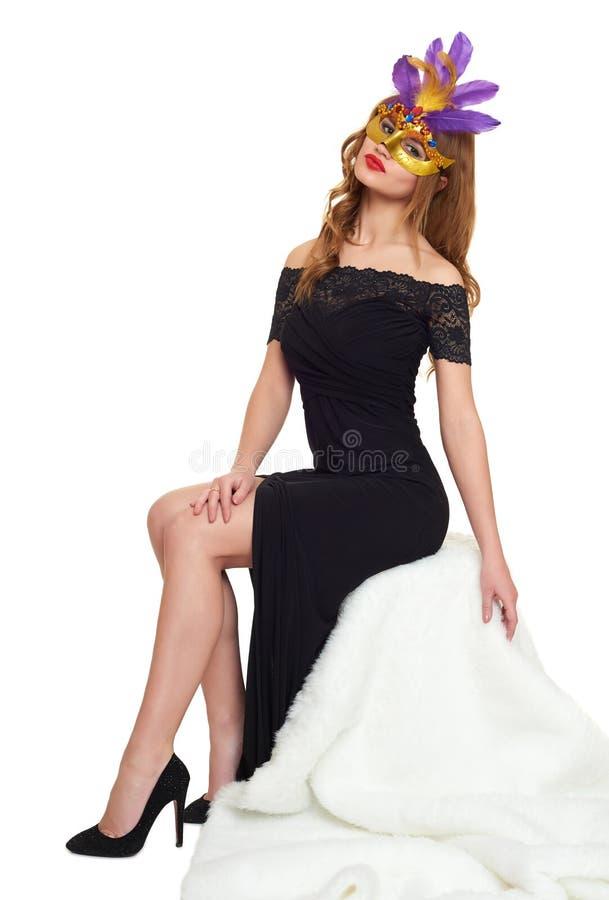 Молодая женщина в черных мантии вечера и маске масленицы Сидите на белом мехе Праздник и концепция партии стоковое изображение
