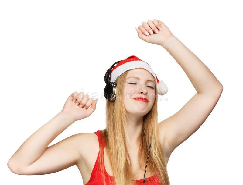 Молодая женщина в шляпе Санта Клауса и наушники принимают удовольствие от стоковое изображение