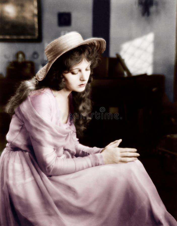 Молодая женщина в шляпе сидя и смотря унылый (все показанные люди более длинные живущие и никакое имущество не существует Warrant стоковые изображения rf