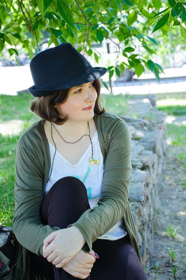 Молодая женщина в шляпе сидя на каменной границе стоковое фото rf