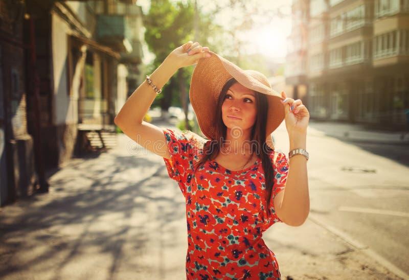 Молодая женщина в шляпе стоя на улице стоковые фото