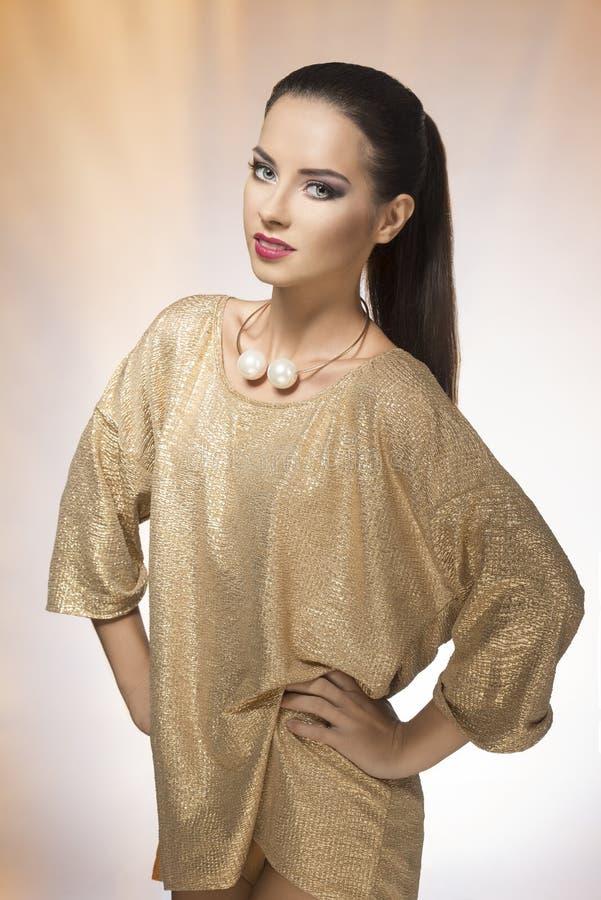 Молодая женщина в spakling платье золота стоковое изображение rf