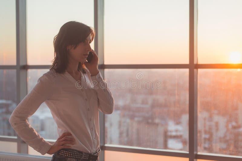 Молодая женщина говоря используя сотовый телефон на офисе в вечере Женская сконцентрированная коммерсантка, смотрящ вперед стоковое изображение