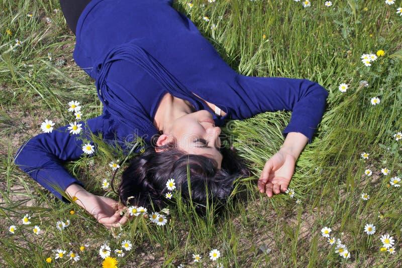 Молодая женщина лежа в лужке стоковое фото rf
