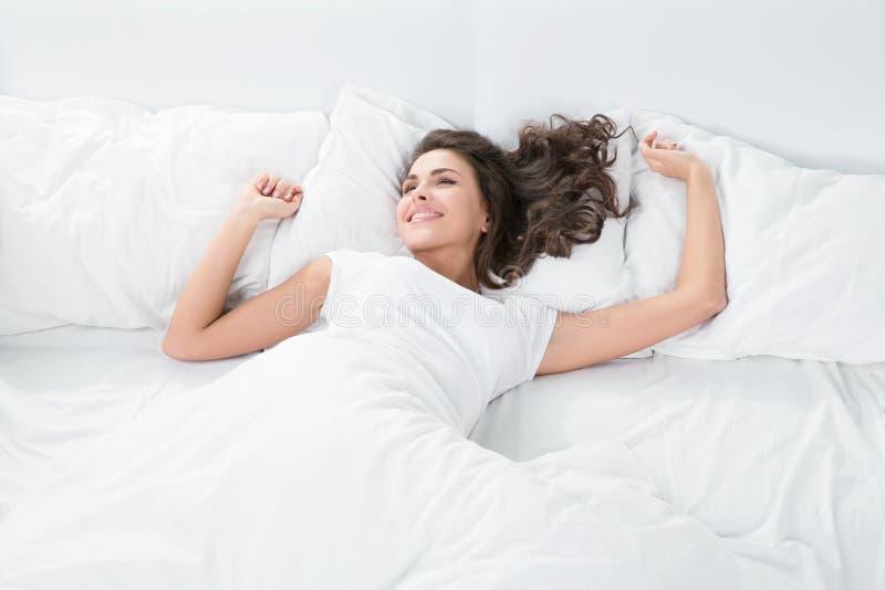Молодая женщина лежа на белом белье в кровати стоковые изображения