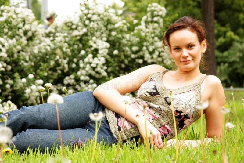 молодая женщина лежа на зеленой лужайке стоковое фото rf