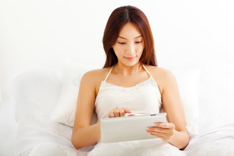 Молодая женщина лежа на кровати используя ее ПК таблетки в ее bedroo стоковые фото