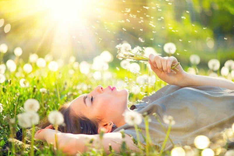 Молодая женщина лежа на поле в зеленой траве и дуя одуванчике стоковая фотография rf