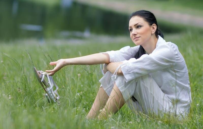 Молодая женщина держа ее сандалии стоковая фотография rf