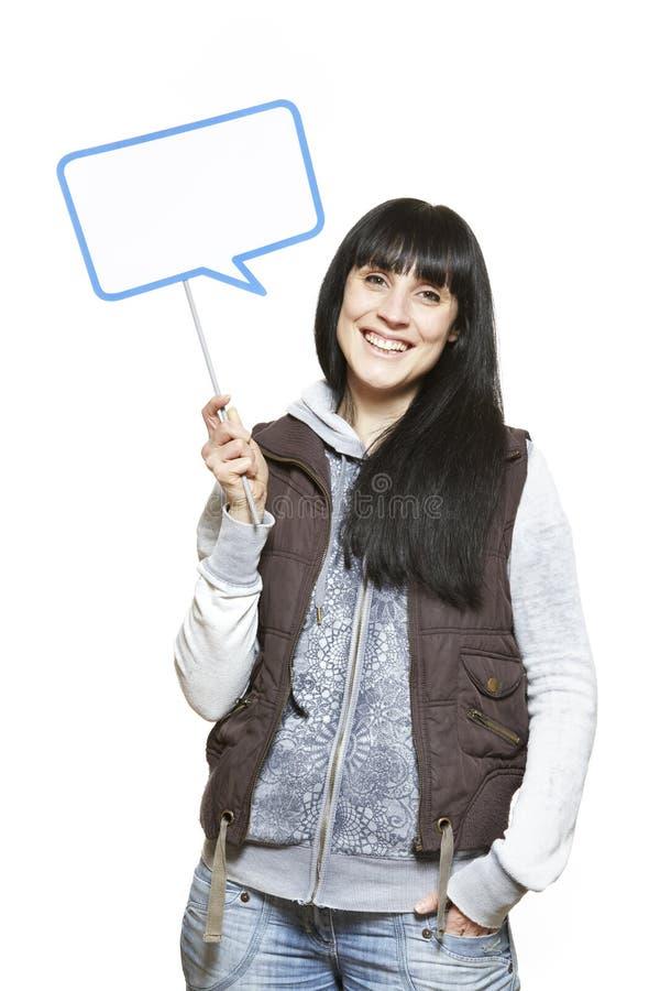 Молодая женщина держа усмехаться знака пузыря речи стоковые фото
